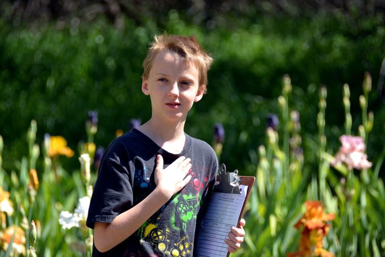Close-up of boy holding clipboard at park