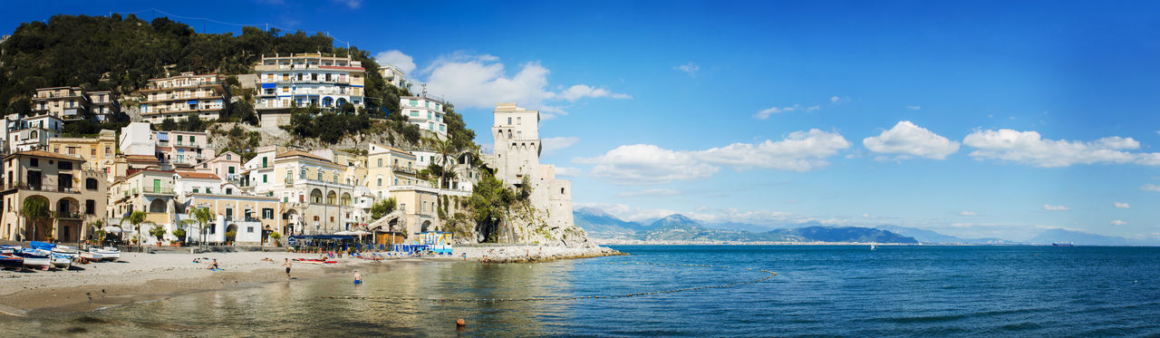 Cetara, Italy - October 2, 2013: Cetara small beach village on the Amalfi Coast, LA beach is defended by an ancient Saracen tower. Bathers on the beach on a warm October day. In the background you can see the city of Salerno Architecture Beauty In Nature Blue Built Structure Cloud Cloud - Sky Coastline Day Leisure Activity Lifestyles Mixed Age Range Nature Outdoors Scenics Shore Sky Tourism Tourist Tranquility Travel Destinations Vacations Water