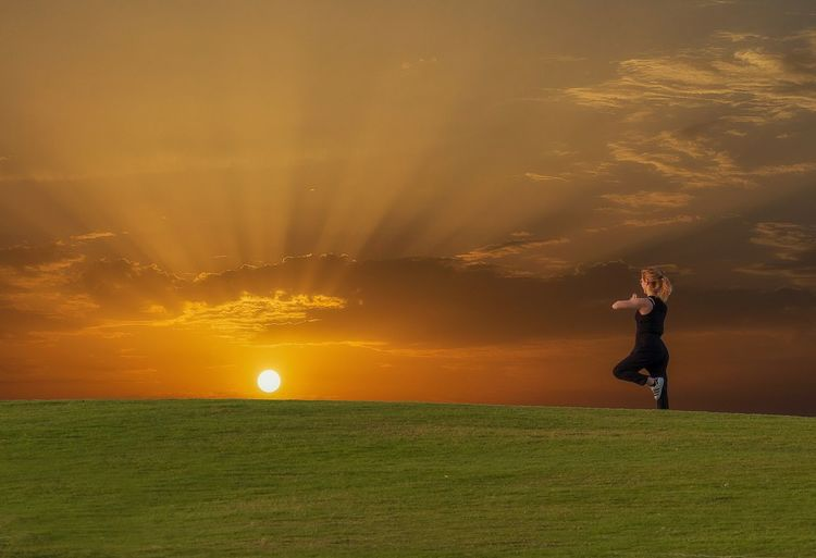 Sunset yoga One Person Leisure Activity Grass Full Length Nature Standing Sky Playing Sunset Real People Field Sunlight Land Sport Plant Women Green Color Child Lifestyles Outdoors The Great Outdoors - 2019 EyeEm Awards