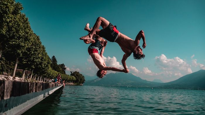 LOW ANGLE VIEW OF PEOPLE JUMPING OVER WATER AGAINST SKY