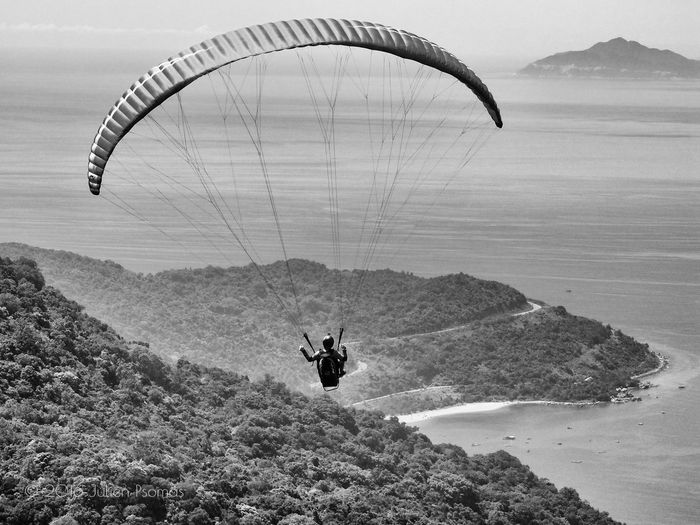 Rear view of man paragliding above mountains against sea