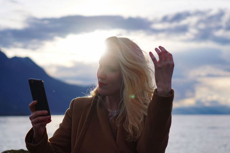 Mid adult woman using smart phone against lake