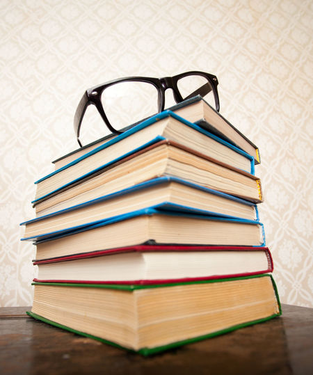 A pile of books for studying and black glasses on the table Back To School Book Close-up Document Education Eyeglasses  Learning Literature No People Paper Pile Research Stack Table Textbooks