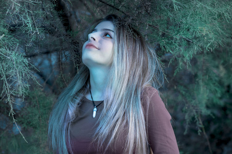 Close-up of woman looking away in forest