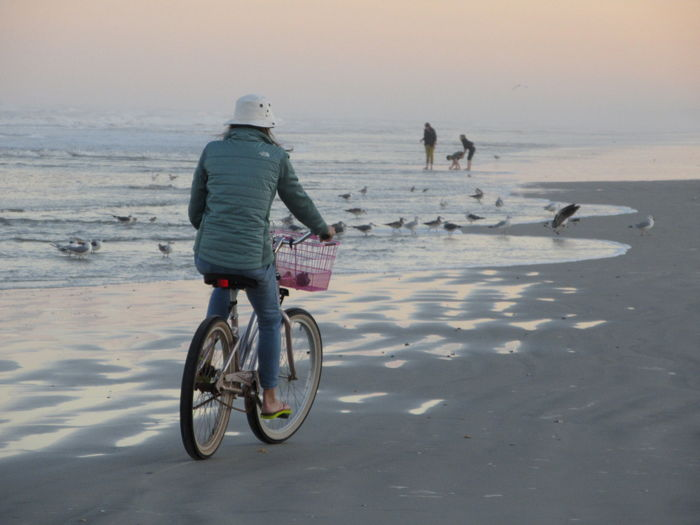 Woman riding bicycle at beach during sunset