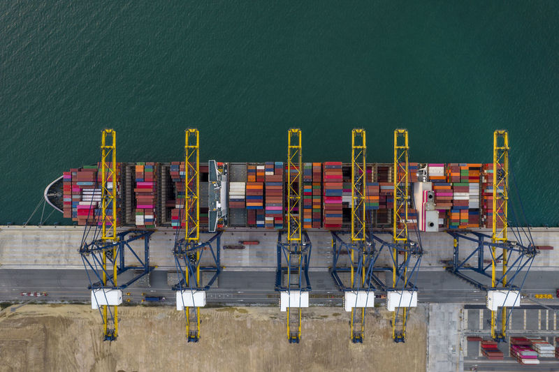 Aerial top view of crane loanding cargo container to container ship in the international terminal