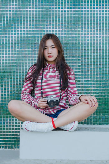 Portrait of young woman sitting with camera against tiled wall