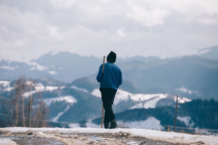 Rear view of man standing on mountain during winter