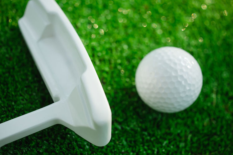 Golf ball with putter on green course. Image with selective focus Golf Golf Course Golfing Golfing Fun Green LINE Lifestyle PUTT Ball Club Cup Game Golf Ball Golf Club Golfcourse Golfer Grass Lawn Leisure Outdoor Play Putter Putting Sport White