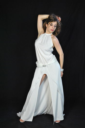 Full length of beautiful fashion model standing against black background