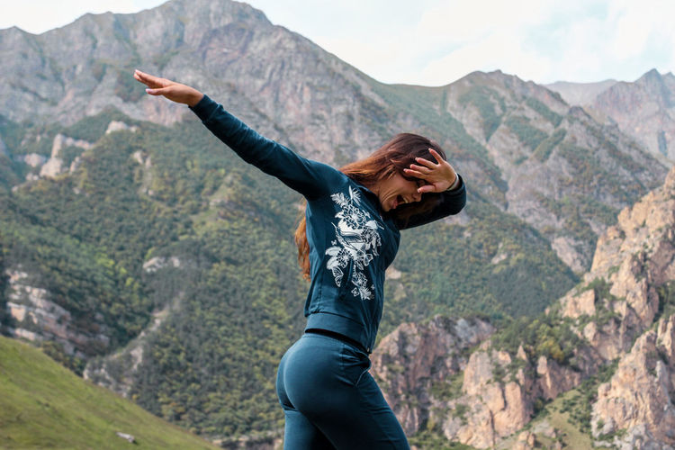 Young woman doing dab dance against mountain range