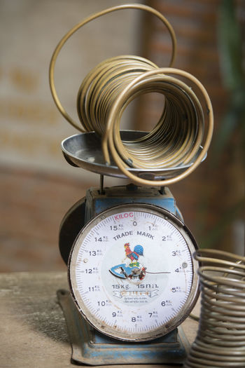 High angle view of coiled metal with old-fashioned weight scale on table