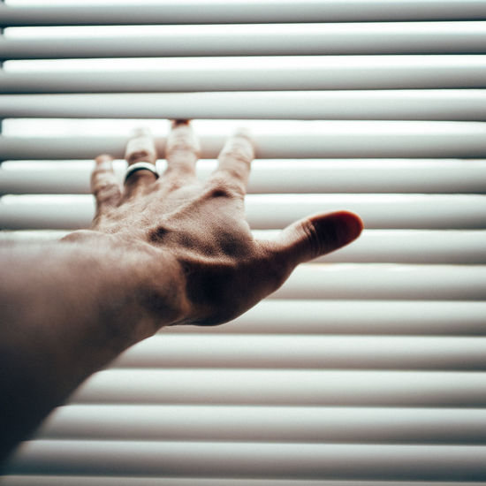 Cropped hand reaching through window blinds