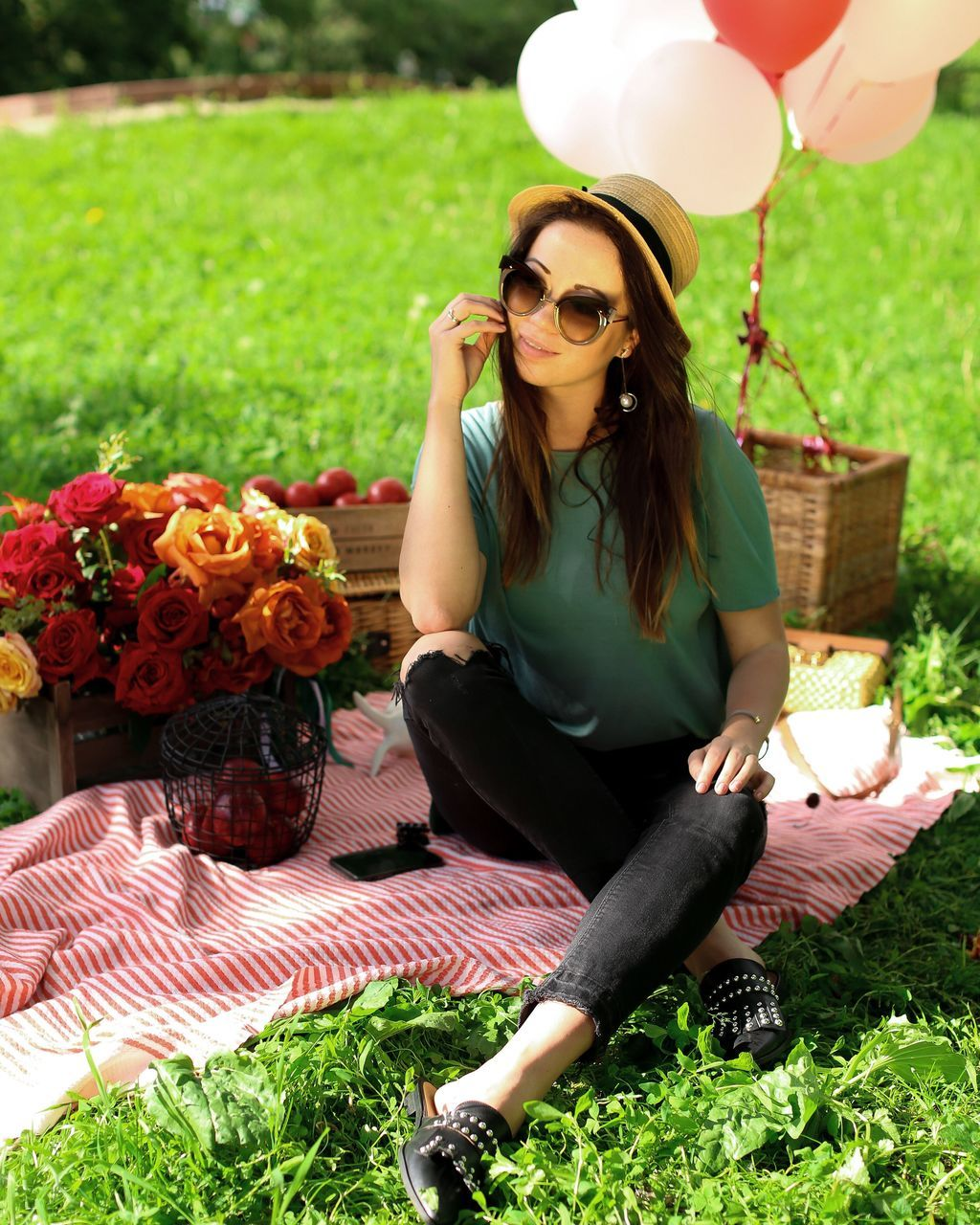 grass, flower, one person, full length, real people, front view, lawn, sunglasses, young women, outdoors, casual clothing, young adult, beautiful woman, leisure activity, day, lifestyles, park - man made space, sitting, smiling, nature, sun hat, plant, happiness, beauty in nature, portrait, freshness