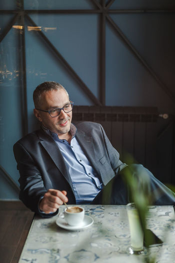 Thoughtful businessman with coffee on table sitting at restaurant
