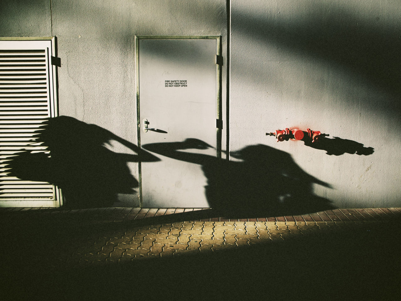 Shadow of two people against building exterior