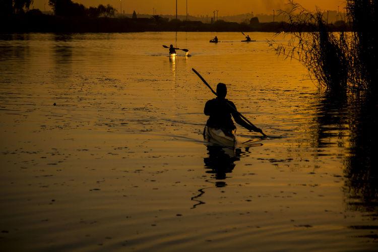 Rear view of silhouette man fishing in sea