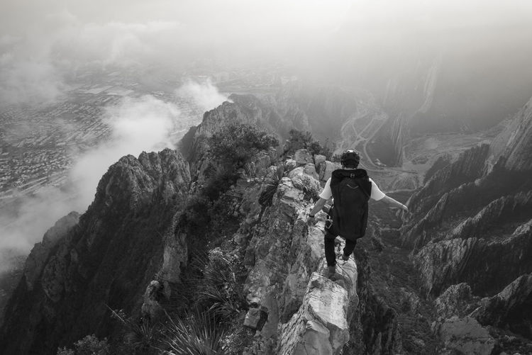 Rear view of man on rocks against mountains