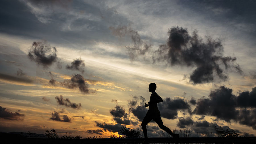 Silhouette boy running against sky during sunset