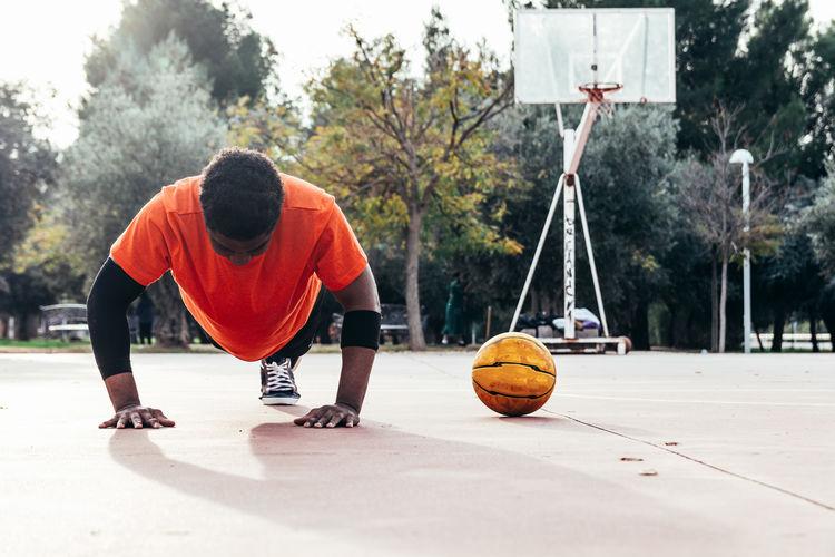 Portrait of a black afro boy doing push-ups on an urban basketball court.