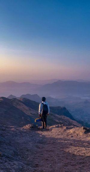 Full length of man on mountain against sky during sunset
