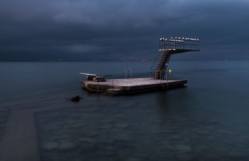 Floating platform in sea against cloudy sky at dusk
