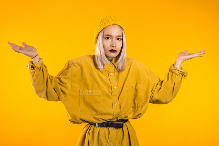 Portrait of woman standing against yellow background