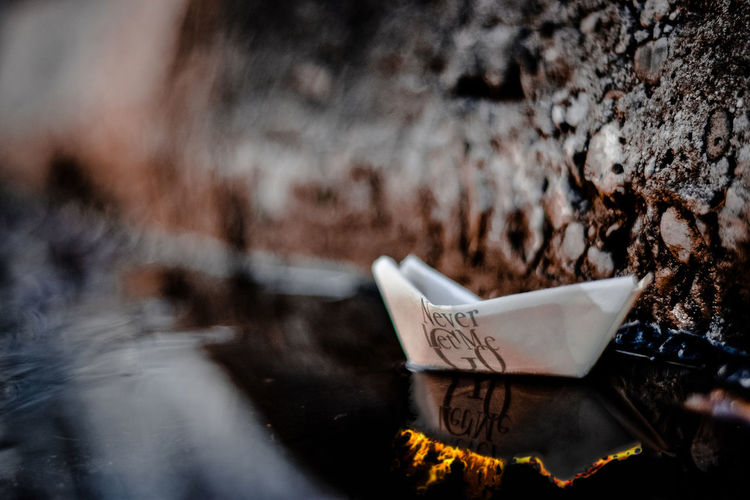 Close-up of paper boat with text in water