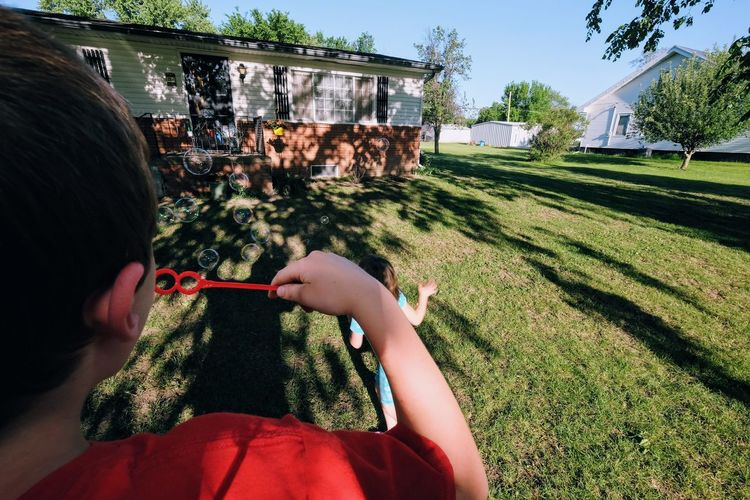 Rear view of boy blowing bubbles while playing with sister at yard