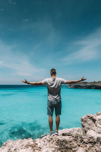 Rear view of young man standing against sea
