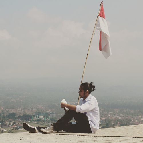 Man reading book while sitting by indian flag against sky in city