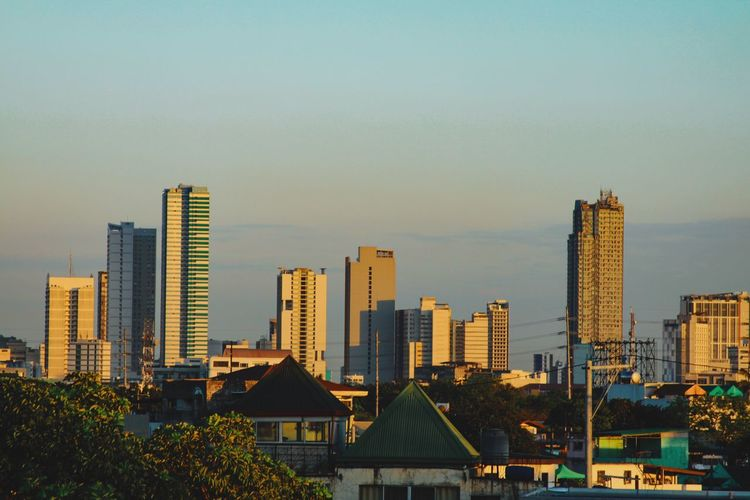 Buildings in city against clear sky during sunset