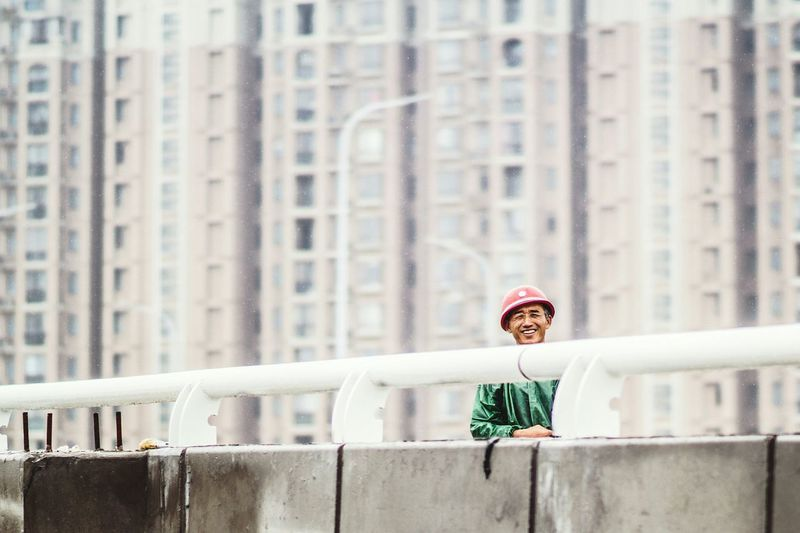 Portrait Of Happy Man Standing On Bridge Against Buildings