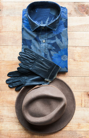 Table Indoors  No People Still Life Clothing Wood - Material Blue High Angle View Wood Flooring Close-up Personal Accessory Hat Shoe Directly Above Folded Hardwood Floor Textile Group Of Objects Pants Jeans Garment Small Group Of Objects