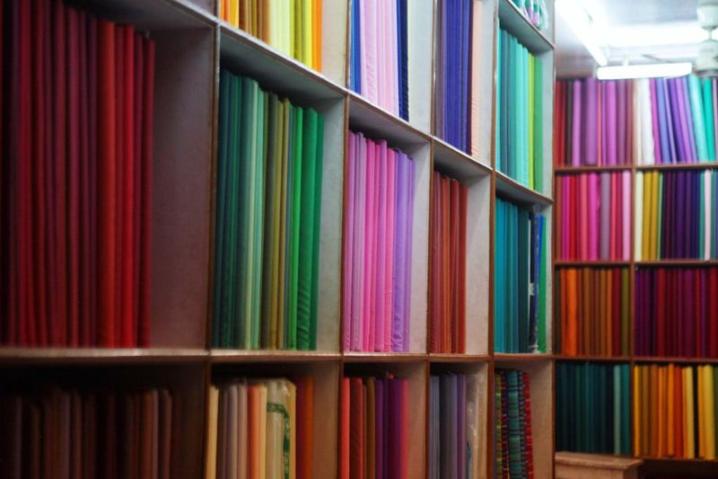 Multi Colored Fabrics Arranged On Shelves At Shop