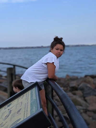 Portrait of girl standing by railing at beach against sky