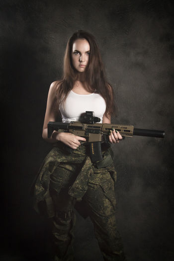 Adult Beautiful Woman Black Background Clothing Front View Government Gun Hair Hairstyle Holding Indoors  Long Hair Looking At Camera One Person Portrait Rifle Standing Studio Shot Uniform Weapon Young Adult Young Women