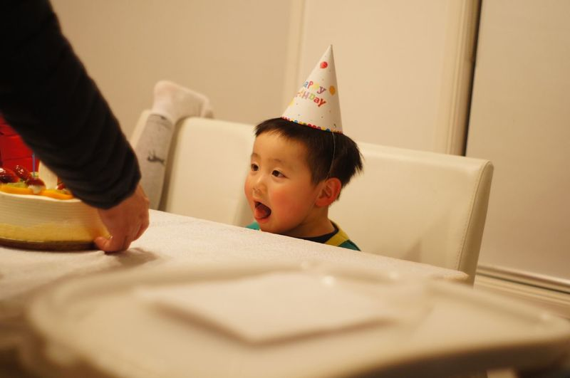 Thoughtful boy wearing party hat while sitting at table during birthday