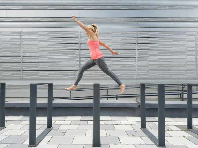 Hurdles The Color Of Sport Outdoors Urban Geometry Sportswear Pink Top Athletic Hurdles Race Doing Sport Healthy Lifestyle Pedestrian Walkway Young Adult Running Jumping Woman Shades Of Grey Facades Silver  Wall Modern Architecture City Building Exterior EyeEm Best Shots Summer In The City Stories From The City