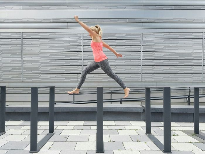 Hurdles The Color Of Sport Outdoors Urban Geometry Sportswear Pink Top Athletic Hurdles Race Doing Sport Healthy Lifestyle Pedestrian Walkway Young Adult Running Jumping Woman Shades Of Grey Facades Silver  Wall Modern Architecture City Building Exterior EyeEm Best Shots Stories From The City