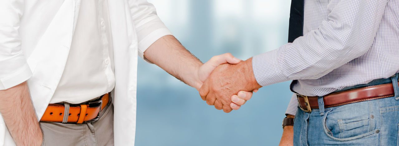 Midsection of doctors shaking hands at clinic