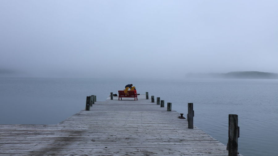 Adirondack chairs on dock in morning mist