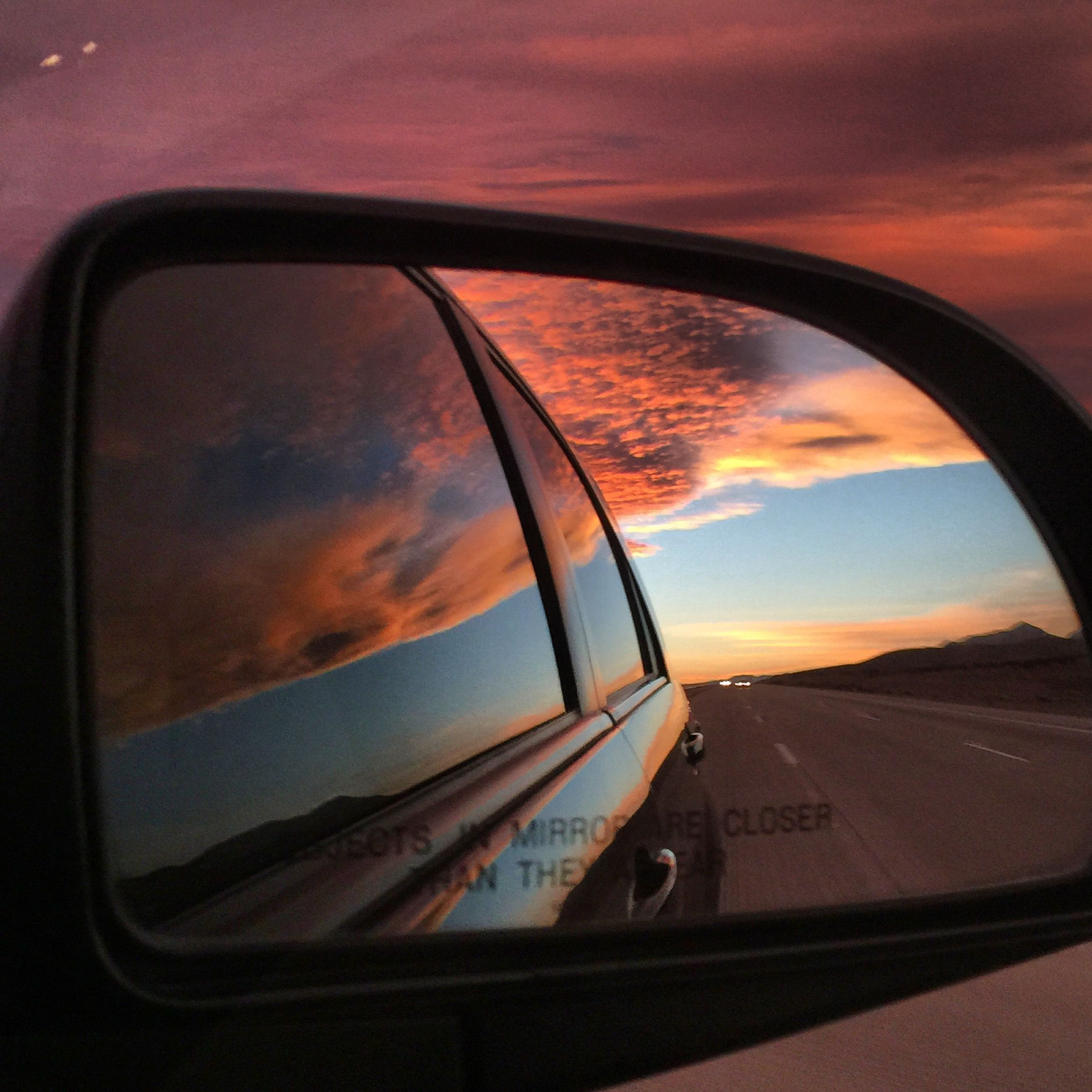 transportation, mode of transport, sunset, sky, car, land vehicle, cloud - sky, side-view mirror, vehicle interior, glass - material, part of, reflection, cloud, transparent, road, travel, cropped, orange color, close-up, car interior