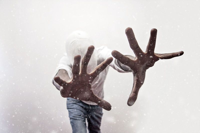 A black man in a mask reaching out to snow Black Man Mask - Disguise Studio Shot Adult Adults Only Snow EyeEm Selects Mask One Person Leisure Activity Men Nature Winter Standing Three Quarter Length Cold Temperature Lifestyles Real People Front View Childhood Human Hand Day White Background Hand Wet Snowing Warm Clothing Fingers Reaching Out Digital Composite