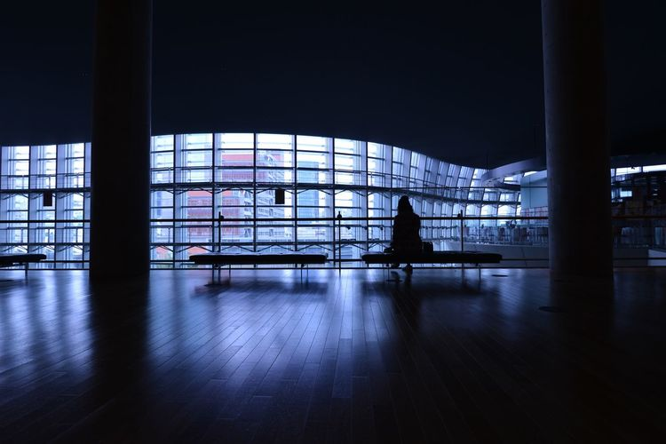 Silhouette woman sitting on bench at airport