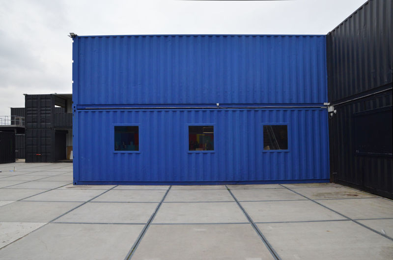 blue and black containers in the harbor Mybestphoto Architecture Building Exterior Entrance Built Structure Blue No People Outdoors Metal Empty Day Sky City Sea Container Closed Building Wall - Building Feature