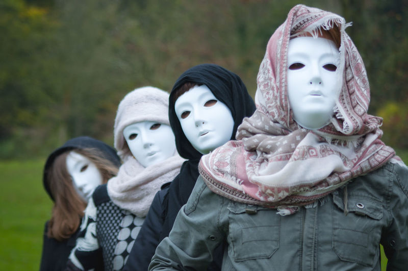 Women covering face with mask at public park