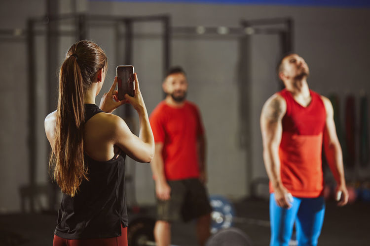 Woman photographing through mobile phone while standing at gym