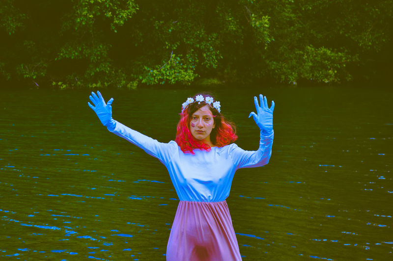 Portrait of young with arms raised standing by lake
