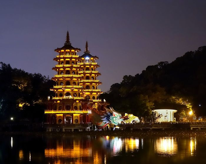 The famous Tiger and Dragon Pagodas at the Lotus Lake in Taiwan Evening Illuminated Kaohsiung, Taiwan Lake Lotus Lake Night Time Pagoda Reflection Temple Travel Destinations Water